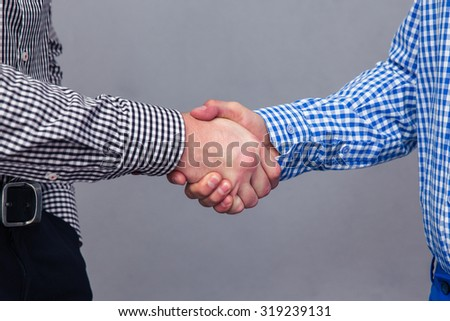 Portrait of a two male hands doing handshake over gray background - stock photo