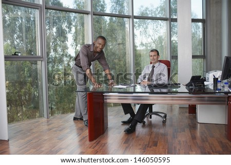 Portrait of a two multiethnic businessmen at desk in office - stock photo