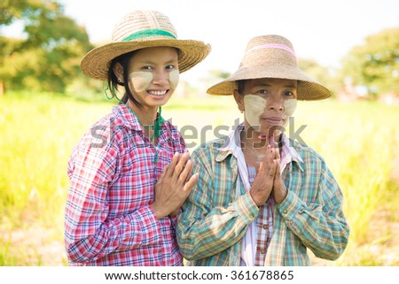 Portrait of a two Myanmar female farmers with thanaka powdered face showing greeting gesture at paddy field.