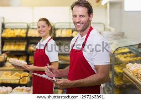 Portrait of a two smiling bakers looking at camera in bakery