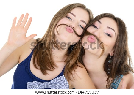 Portrait of a two teen girls have fun and make faces with moustache made of hair pigtail, isolated on white - stock photo