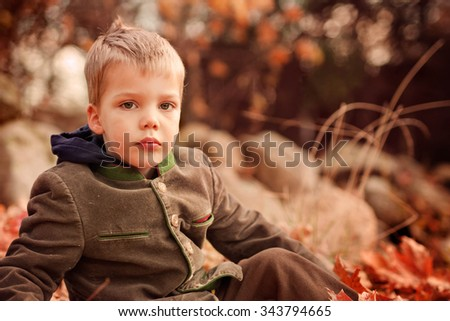 portrait of a two year old blond boy wearing a green jacket sitting on a grass on a warm autumn day - stock photo