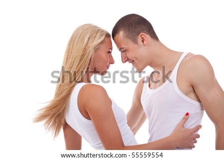 Portrait of a two young beautiful embracing lovers over white - stock photo