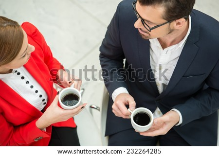 Portrait of a two young business colleagues during a business meeting with  coffee. Top view. - stock photo