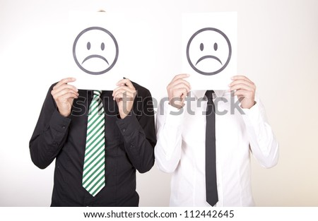 Portrait of a two young men holding sad smiley faces. - stock photo