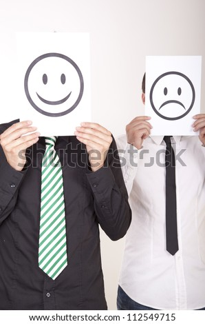Portrait of a two young men holding smiley and sad smiley face.