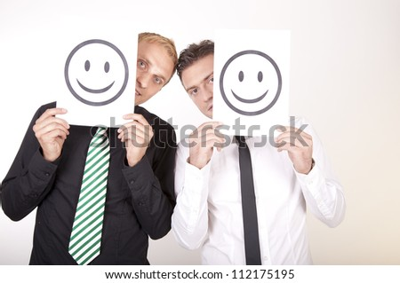Portrait of a two young men holding smiley faces. - stock photo