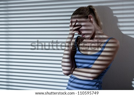 Portrait of a unhappy and depressed young woman in depressive stripe environment, desaturated image