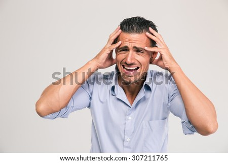 Portrait of a upset businessman standing isolated on a white background - stock photo