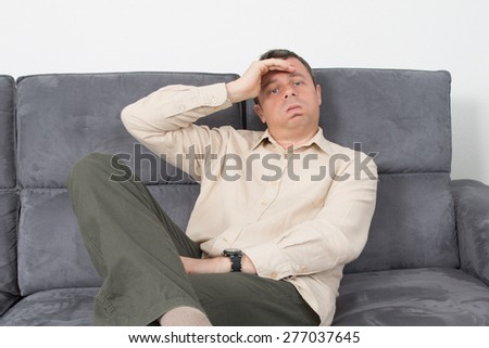 Portrait of a upset  man sitting on sofa in house