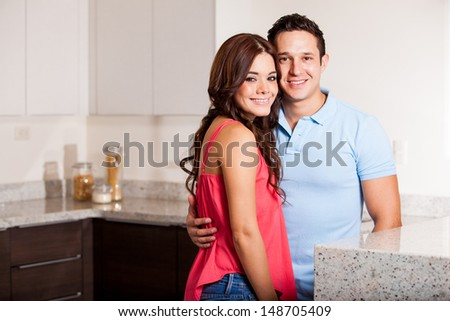 Portrait of a very attractive young couple smiling in the kitchen  - stock photo