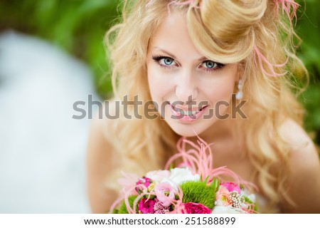 Portrait of a very beautiful bride blonde in a white dress with an unusual stylish hairstyle in the form of hats, and happily smiling, close up - stock photo