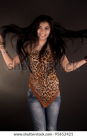 portrait of a very beautiful brunette girl in leopard tunic posing in studio - stock photo