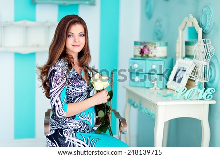Portrait of a very beautiful pregnant girls with big eyes and gorgeous hair in blue dress