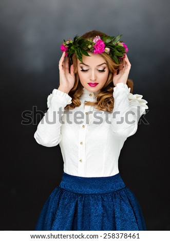 Portrait of a very beautiful sensual glamorous yellow-haired girl in a white blouse and a blue skirt with a wreath of flowers on his head, in the Studio on a dark background