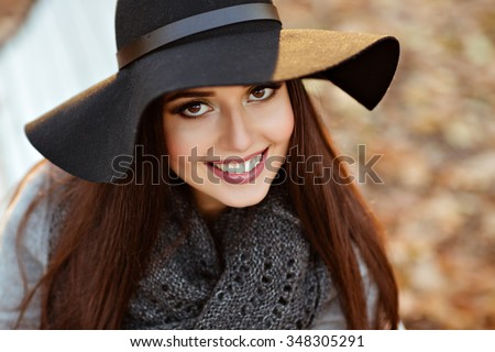 Portrait of a very beautiful young brunette woman with shiny straight hair in a gray coat and black hat smiling on the background of the autumn landscape in the park, close-up - stock photo