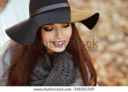 Portrait of a very beautiful young brunette woman with shiny straight hair in a gray coat and black hat smiling with downcast eyes on the background of the autumn landscape in the park, close-up - stock photo