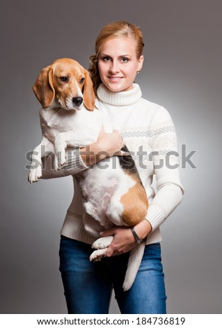 Portrait of a very cute trained beagle and his pretty owner.