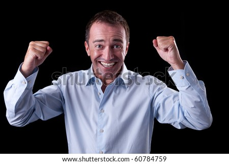 Portrait of a very happy  businessman with his arms raised, on black background. Studio shot - stock photo