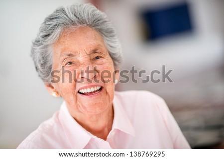 Portrait of a very happy senior woman - indoors - stock photo