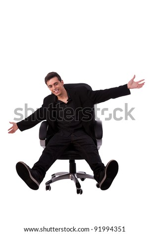 Portrait of a very happy young man, sitting with his arms  open, isolated on white background, studio shot