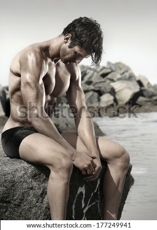 Portrait of a very muscular young man at beach sitting on rock looking down - stock photo