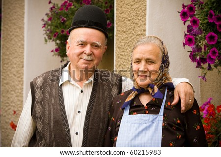 Portrait of a very old couple at country side smiling and having fun. See more images with them. - stock photo