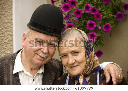 Portrait of a very old smiling couple on country side. See more images with them. - stock photo