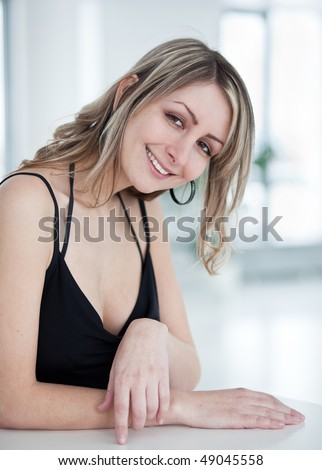 portrait of a very pretty young woman wearing nice black dress, smiling , looking at you - stock photo