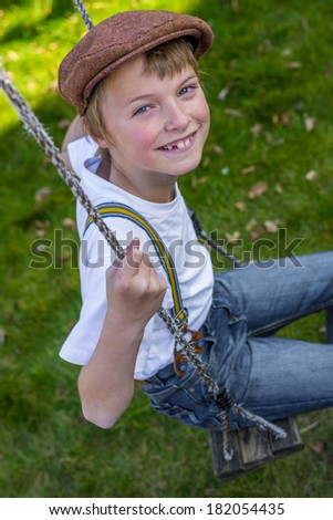 portrait of a vintage looking boy on a swing - stock photo