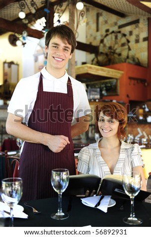 portrait of a waiter and happy costumer at the restaurant