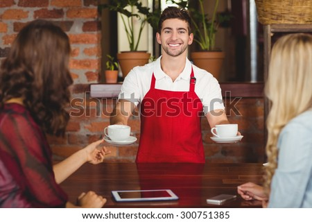 Portrait of a waiter serving coffees to customers at the coffee shop - stock photo