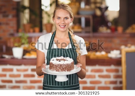 Portrait of a waitress holding a chocolate cake at the coffee shop - stock photo