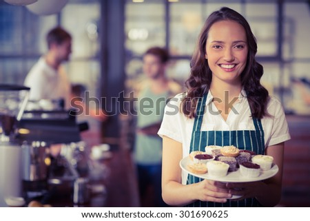 Portrait of a waitress showing a plate of cupcakes at the coffee shop - stock photo