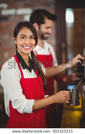Portrait of a waitress steaming milk at the coffee shop - stock photo