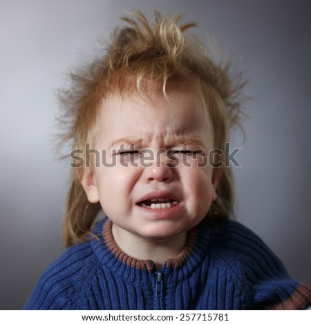 portrait of a weeping baby on a dark background - stock photo