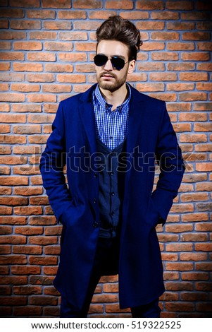 Portrait of a well-dressed imposing man in sunglasses. Fashion hair styling, barbershop. Brick wall background.