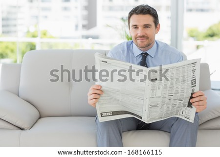 Portrait of a well dressed relaxed young man reading newspaper on sofa in the house