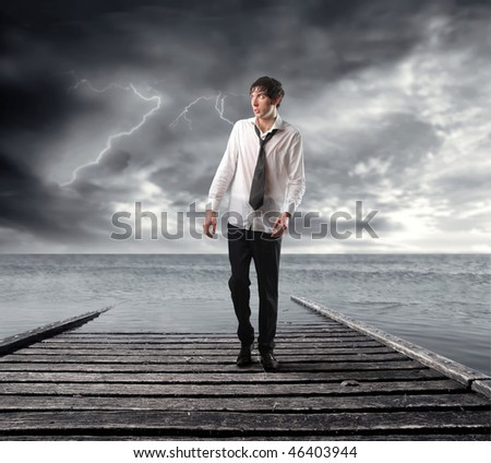 Portrait of a wet businessman walking on a dock looking over the sea with stormy sky on the background - stock photo