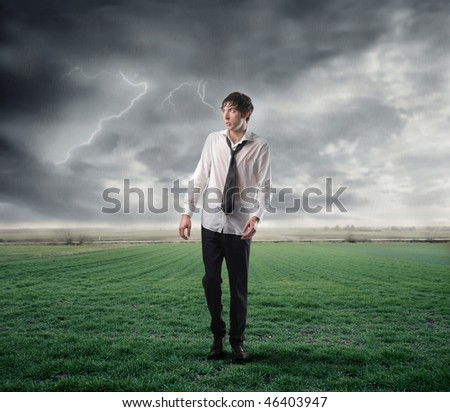Portrait of a wet businessman walking on a green meadow with stormy sky on the background