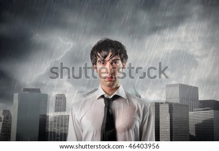 Portrait of a wet businessman with cityscape on the background - stock photo