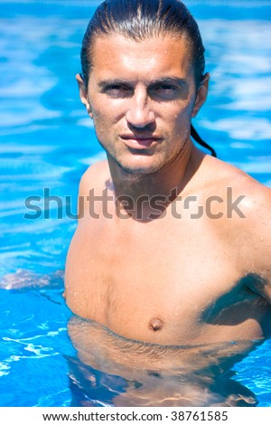 Portrait of a wet man in swimming pool with water drops on face