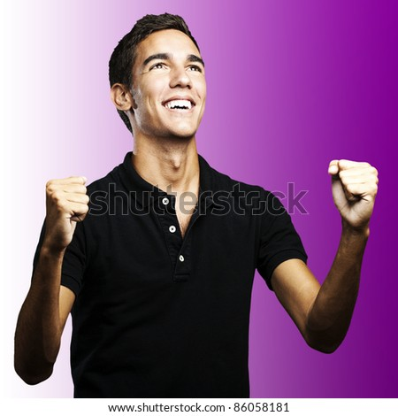 portrait of a winner young man looking up over purple background - stock photo