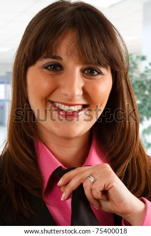 Portrait of a woman adjusting her tie - stock photo
