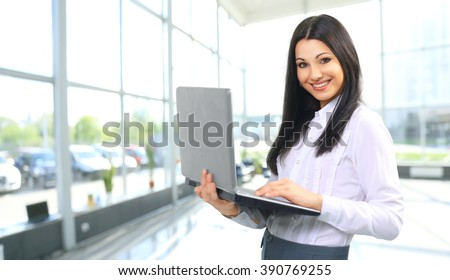 portrait of a woman administrator with laptop on background of o - stock photo