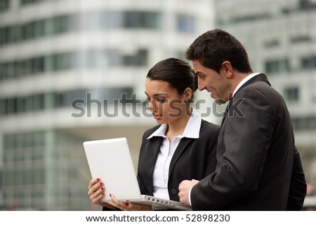 Portrait of a woman and a man in front of a laptop computer - stock photo