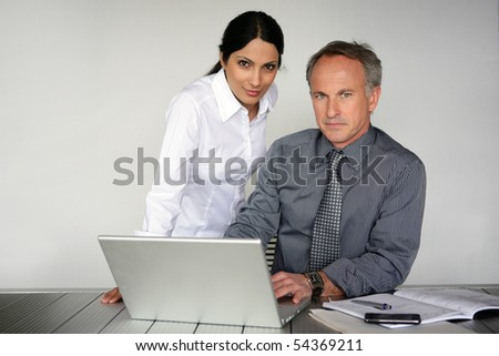 Portrait of a woman and a man in suit in front of a laptop computer - stock photo
