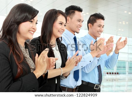 Portrait of a woman and man office workers  clapping celebrating success in the office - stock photo