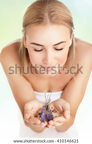 Portrait of a woman at spa beauty salon, holds in hands lavender and sea salt, enjoying aromatherapy herbal anti-stress treatment for health of mind and soul, body skin face and hair care - stock photo
