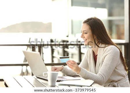 Portrait of a woman buying on line or booking hotel with a laptop and credit card on the beach in vacations. E commerce concept - stock photo